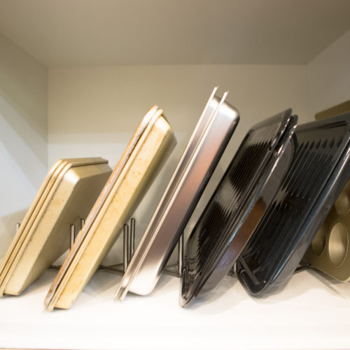 Sheet pans lined vertically in cabinet with accordian organizer