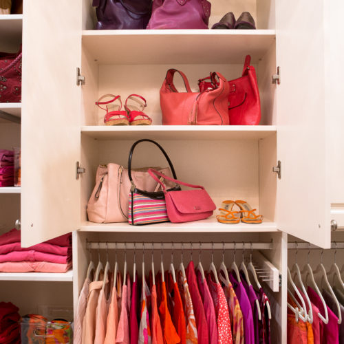 Organized handbags, shoes and clothes in walk in closet