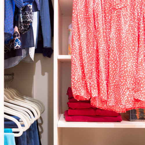 Closet with organized, bright colored clothes folded and hung