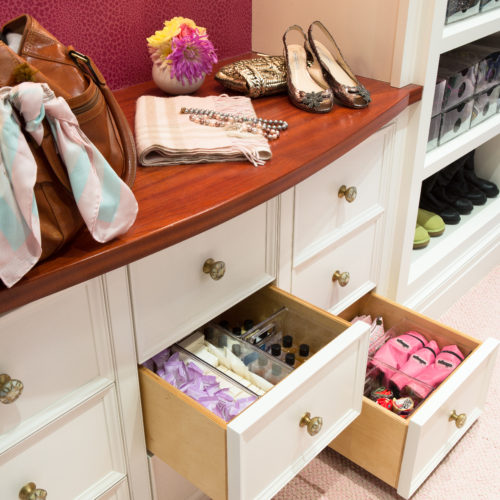 Travel station inside walk in closet with drawers filled with travel products