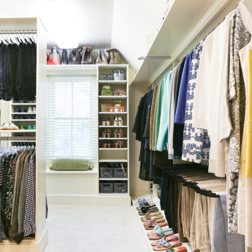 Big closet with organized hanging clothes and lined up shoes