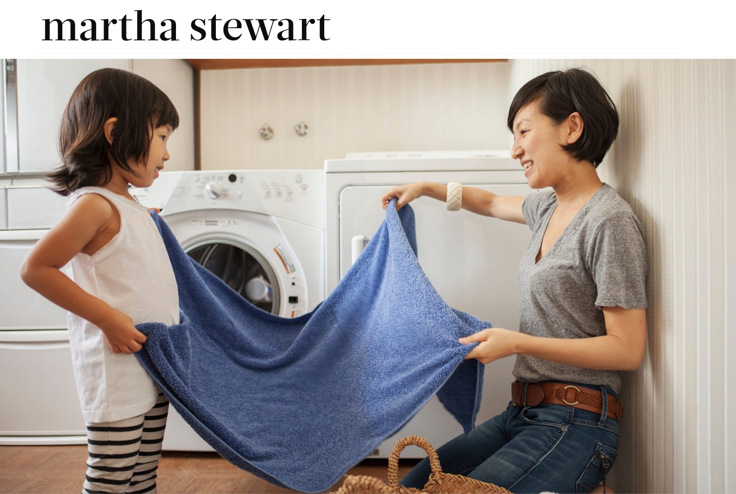 Woman and child folding laundry in laundry room