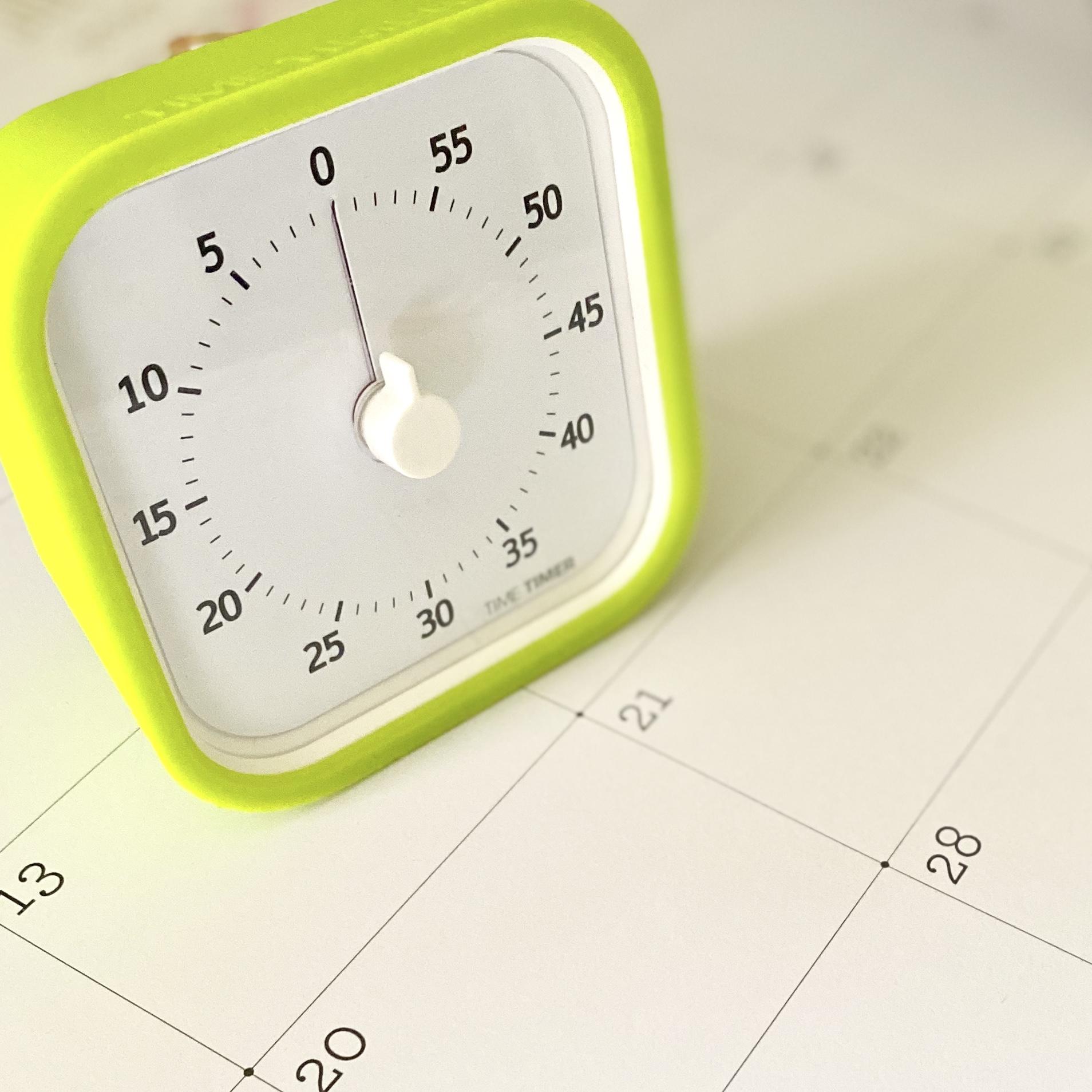 Time timer sitting on a desk top calendar
