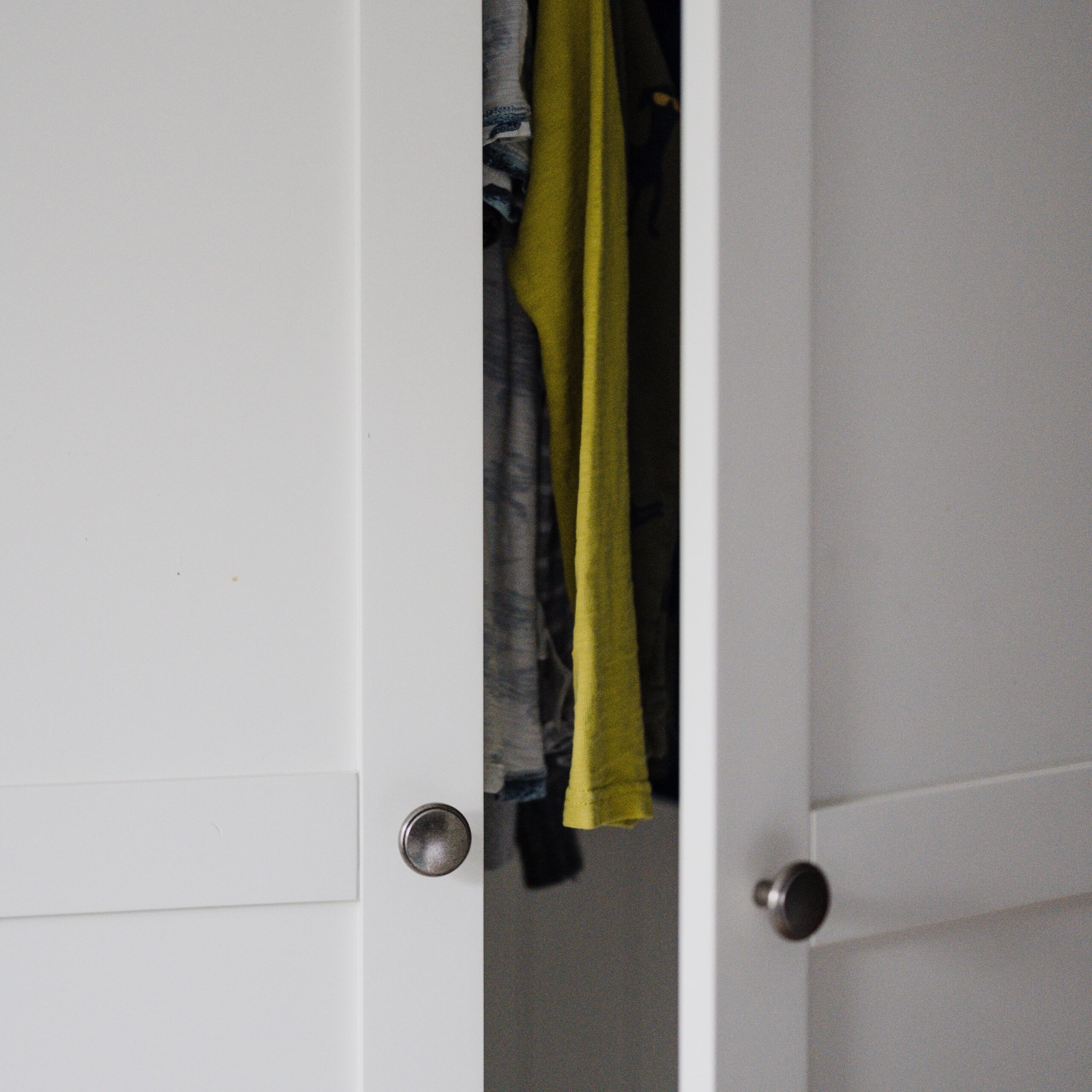 Closet door partially opened with clothes inside