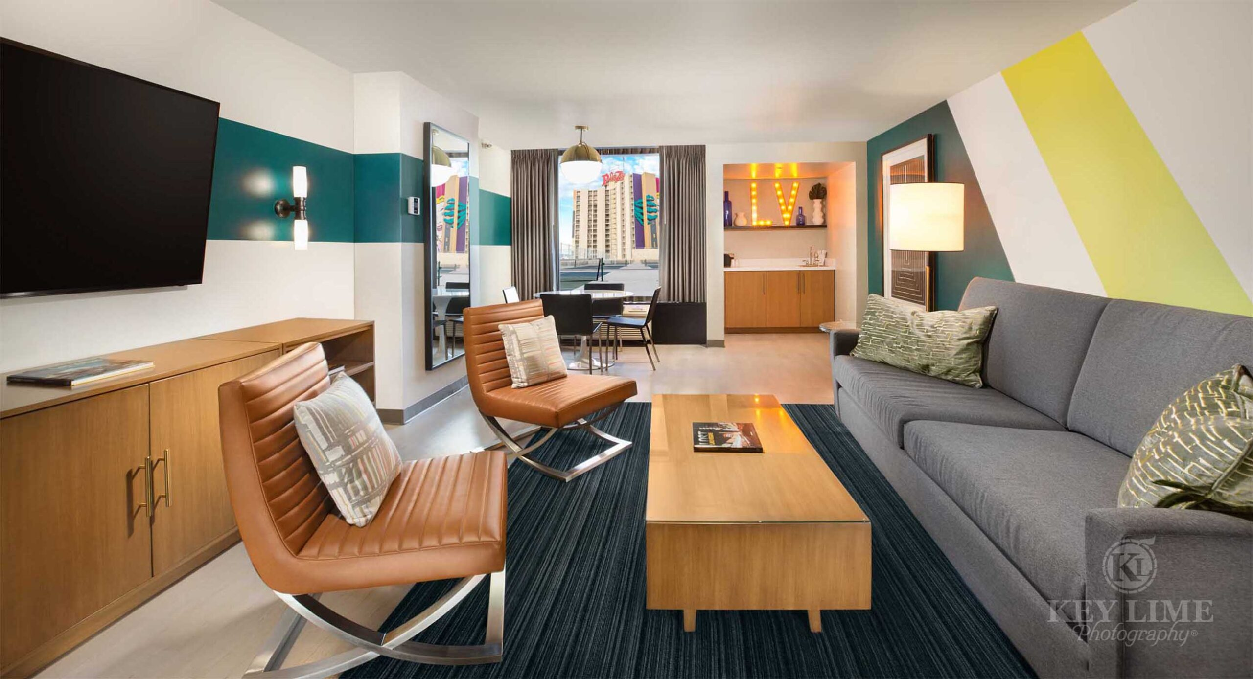 Pool suite inside a Las Vegas hotel. Building photographer image. Bachelor pad with gray sofa and tan, leather chairs.