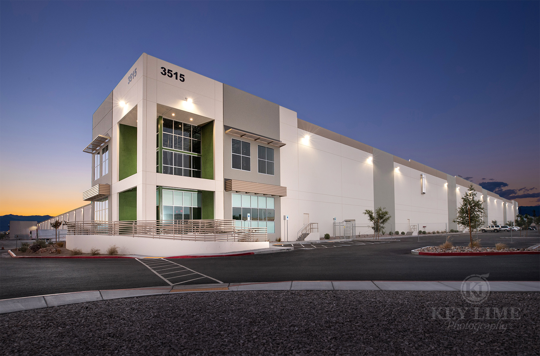 Commercial architecture photographer image of white and green warehouse against a blue twilight sky..
