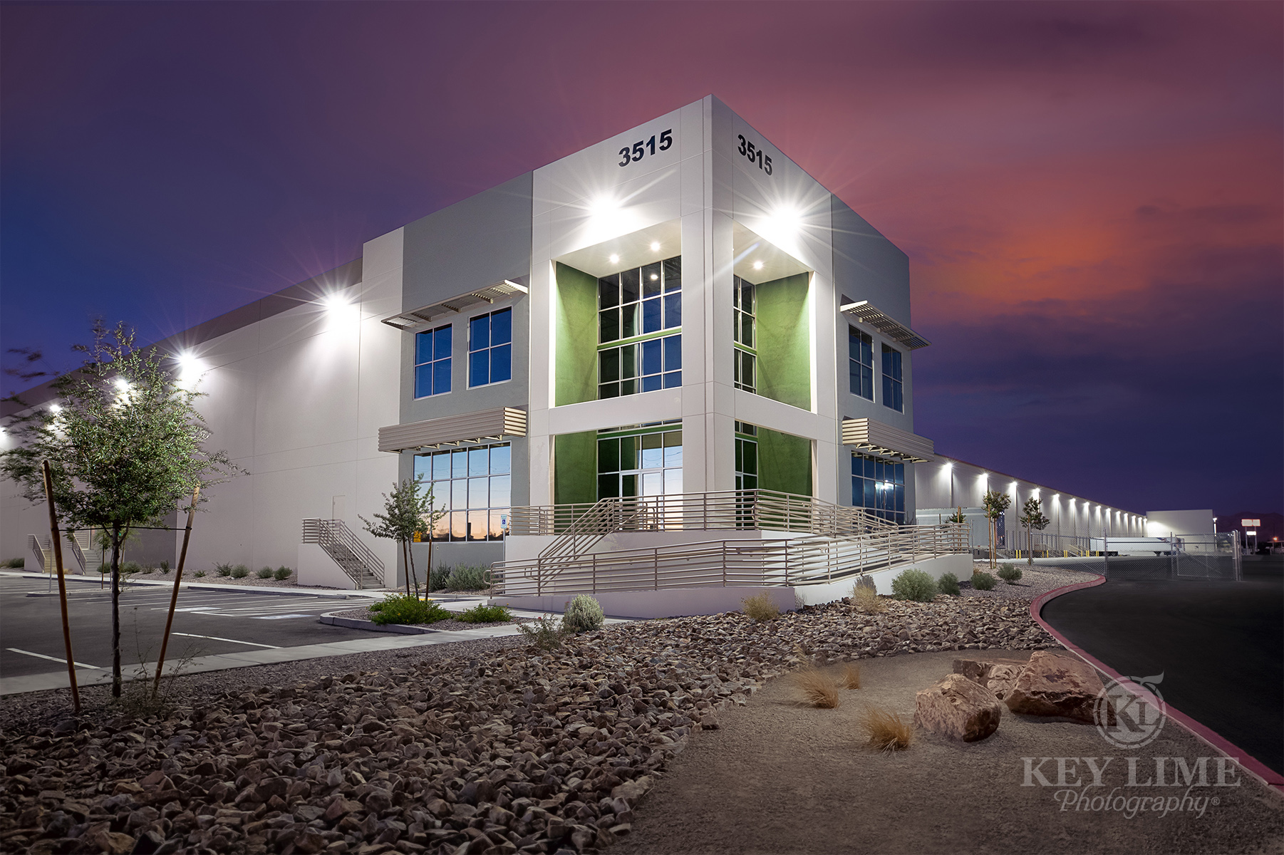 Commercial architecture photographer image of white and green warehouse against a magenta sunset.