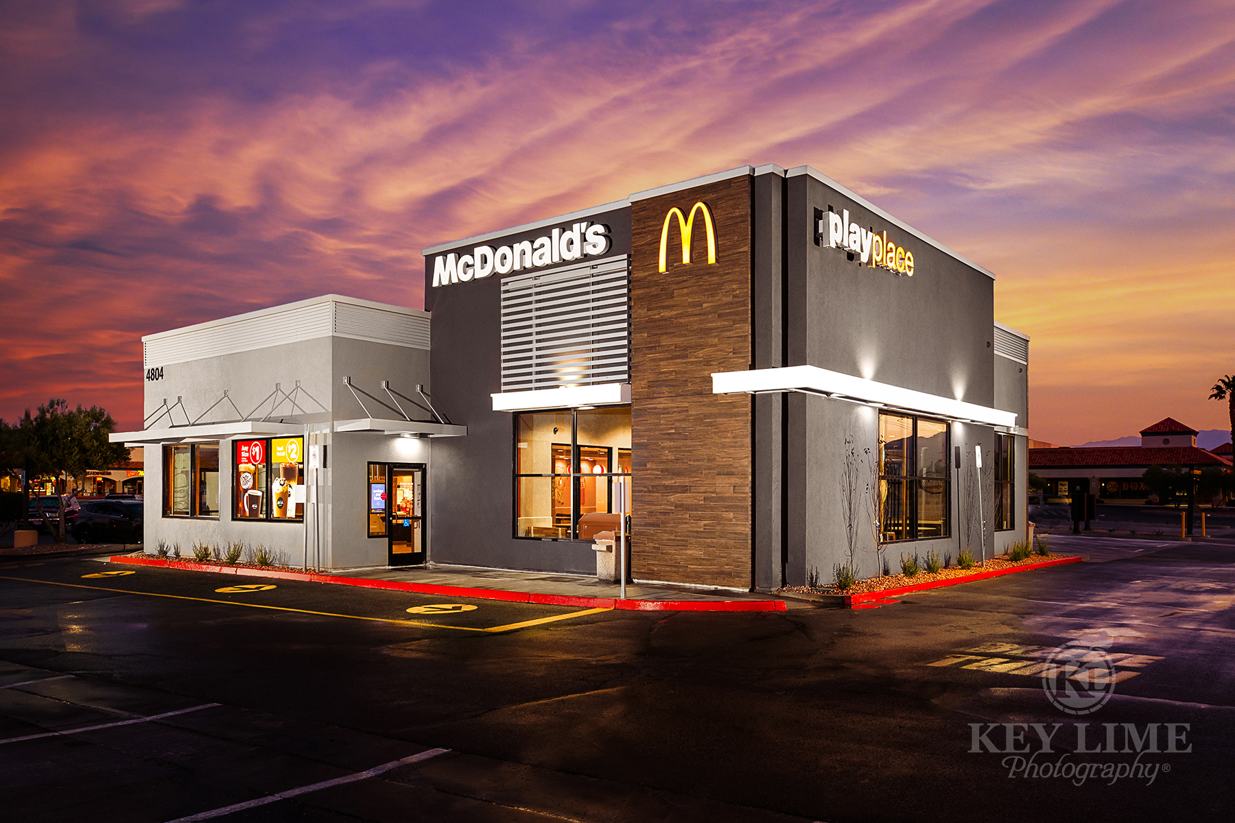 McDonalds commercial architecture photographer photo of restaurant. Warm sunrise with wet, reflective driveway.