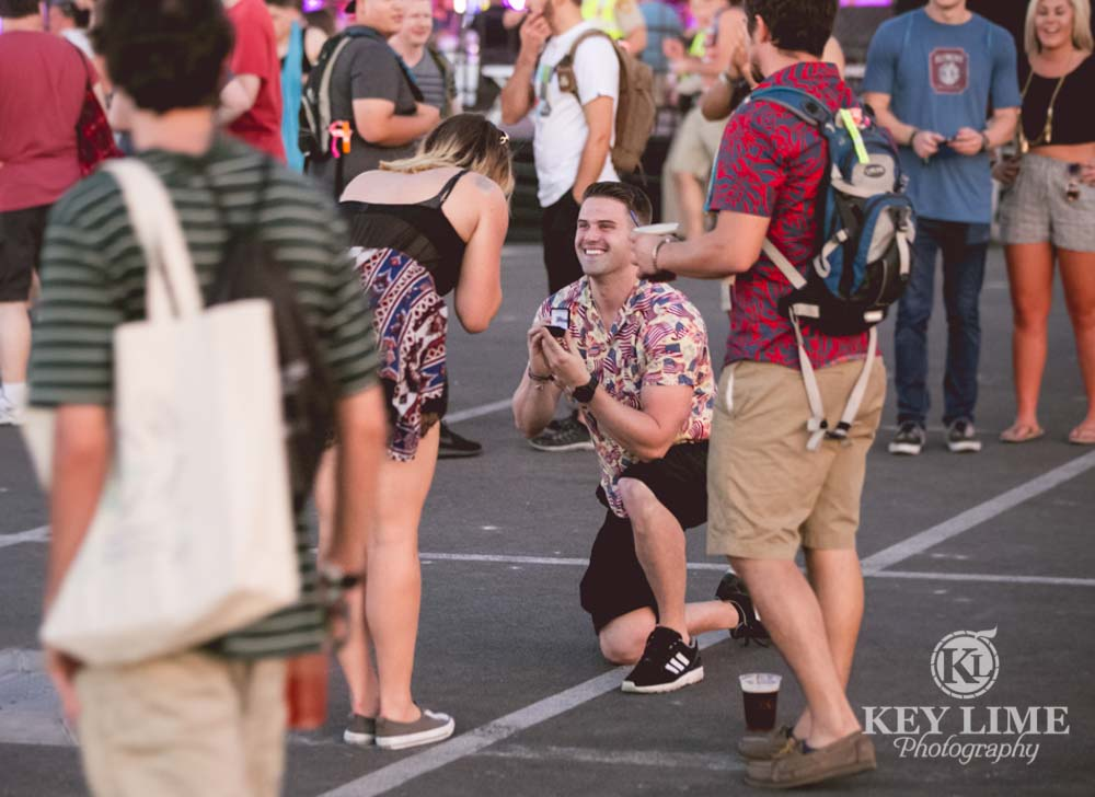 surprise marriage proposal at a festival. guy on one knee, girl in awe.