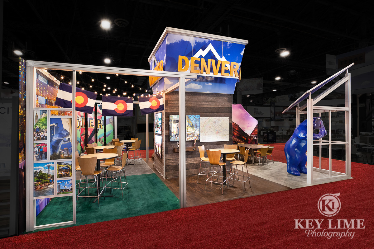 City of Denver trade show booth. Red carpet, blue and white booth with brick accents. Trade show photographer