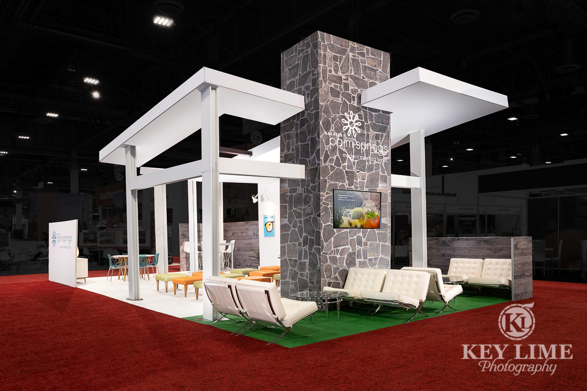 Trade show booth design, hero shot, white structure with stone accent wall. Trade show photographer Key Lime Photo