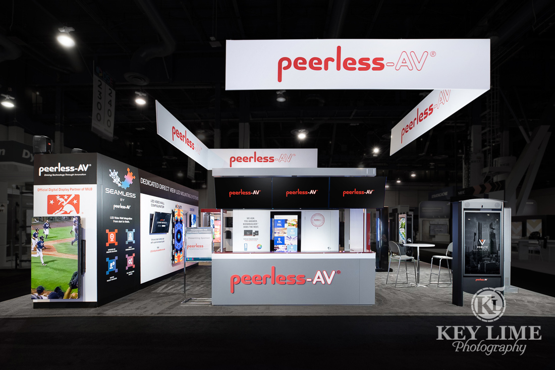 Hero trade show photographer image of white and gray booth design. Red accents, black carpet. PeerlessAV digital displays