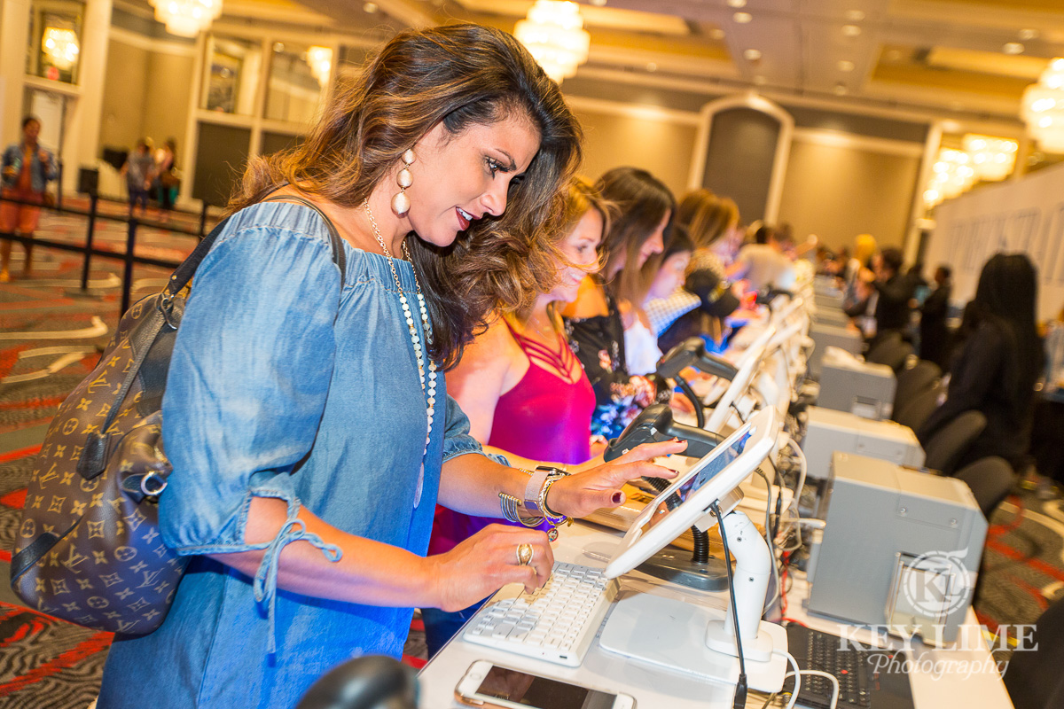 pretty woman entering registration info on an ipad with several other ladies