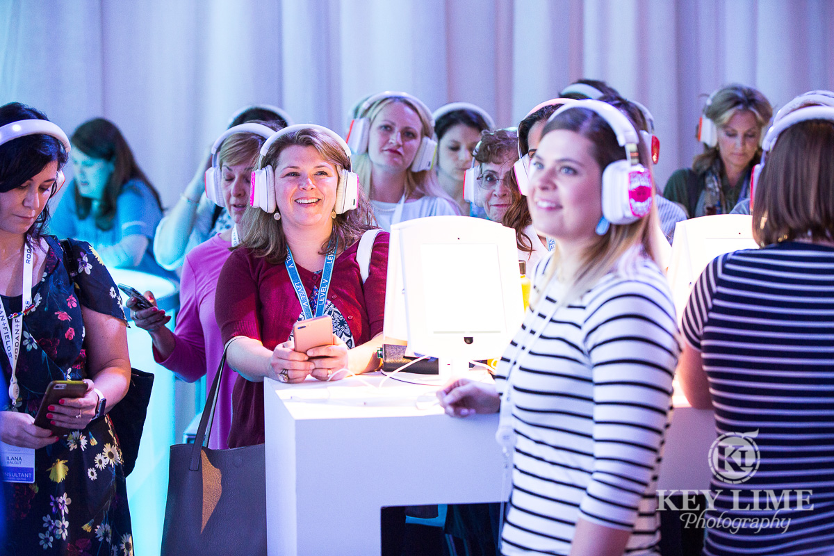Smiling ladies in a learning experience at a trade show. pink and white headphones