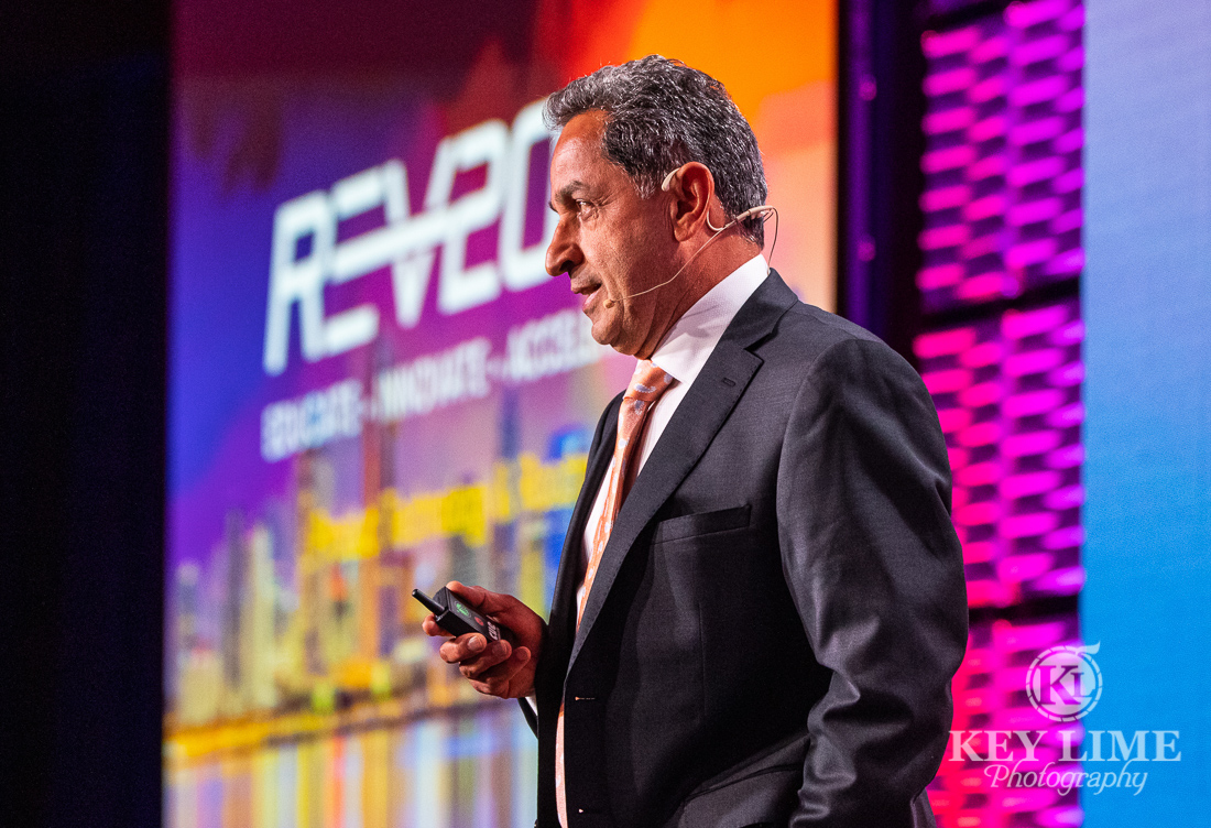 Public speaker with beautiful purple, magenta and orange graphics displayed behind him. Convention photographer image by Key Lime Photography