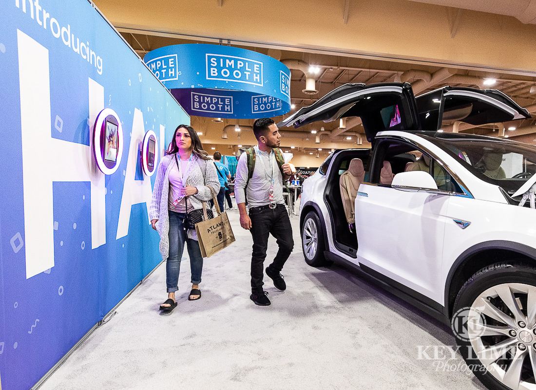 Modern trade show booth photography. Two milenials walk together near Tesla vehicle, automotive