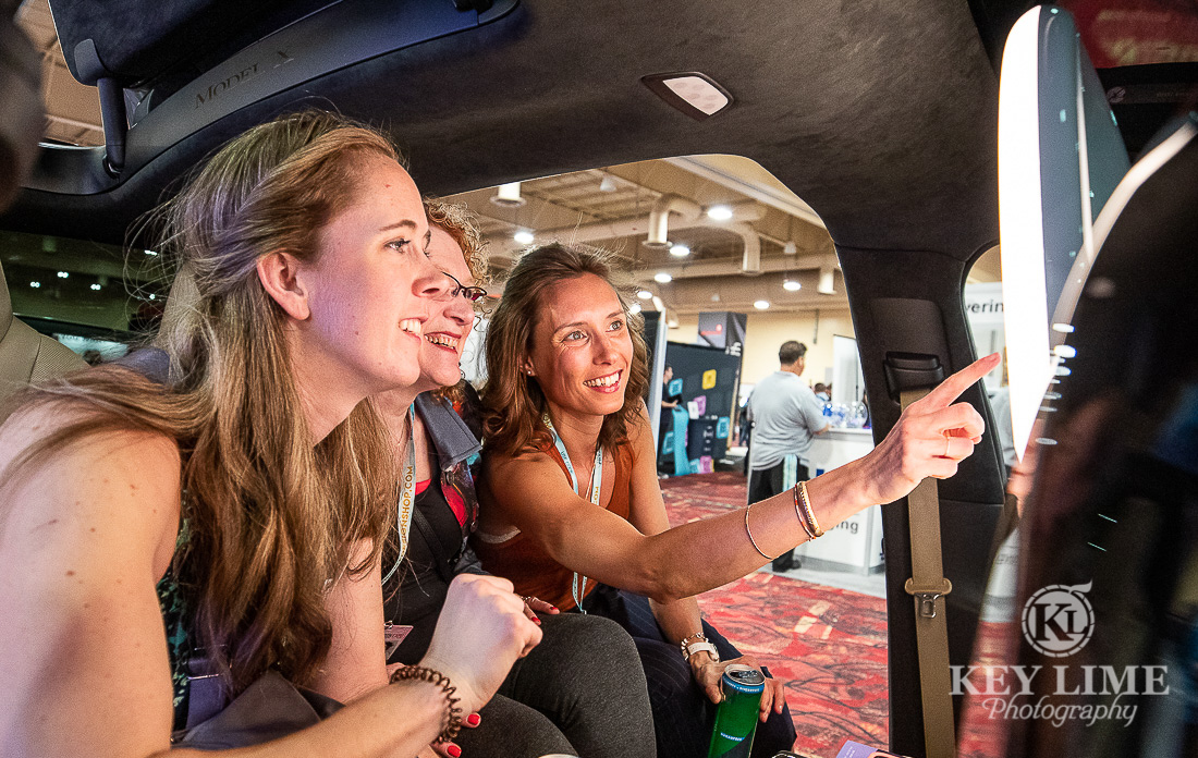 Three women sit in a car engaging with touch screen photo booth experience at a trade show.