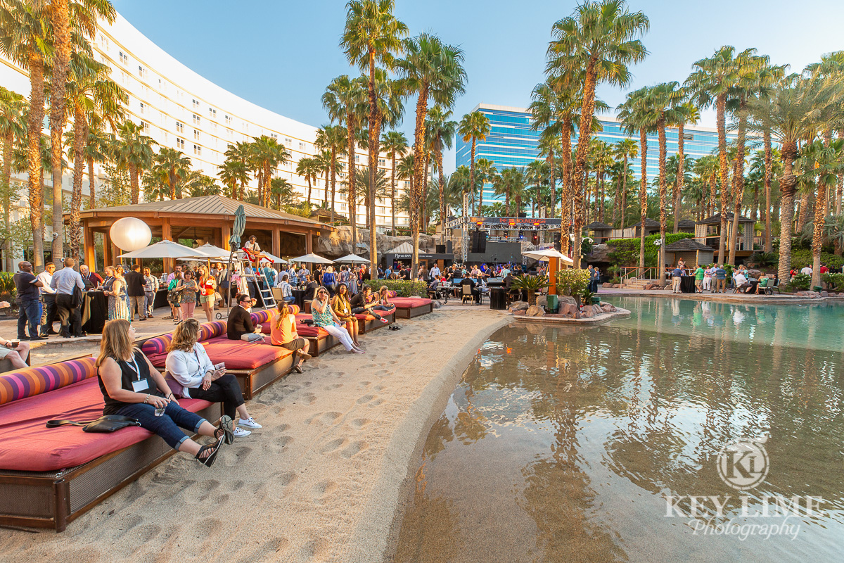 Beautiful outdoor pool reception in Las Vegas. Palm trees and trade show attendants relaxing. Photo by Key Lime Photography