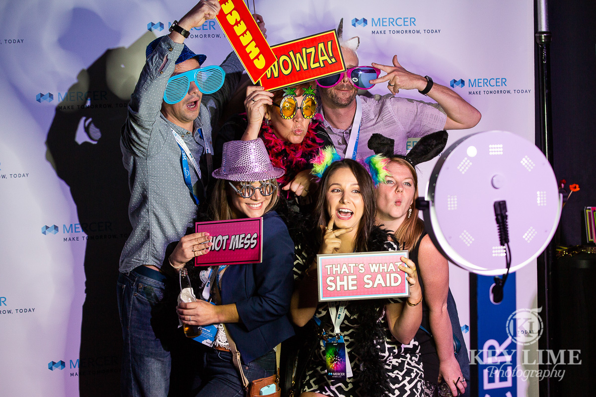 Corporate event photo booth. People laughing and holding photo props. Trade show photography
