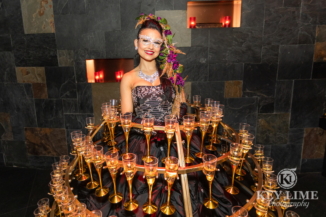 Sexy model posing with dress made of champagne glasses. Trade show entertainment photographer picture.