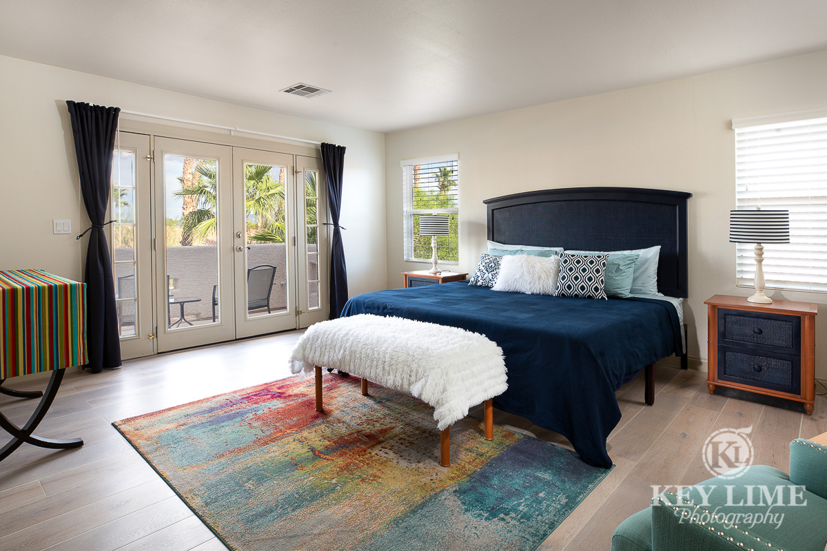 Master bedroom real estate photography. Navy blue king size bed.