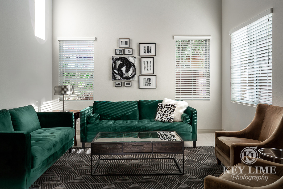 Real estate archtecture photographer image of living room with green couch and brown chairs. Silver wall decor and modern interior design.