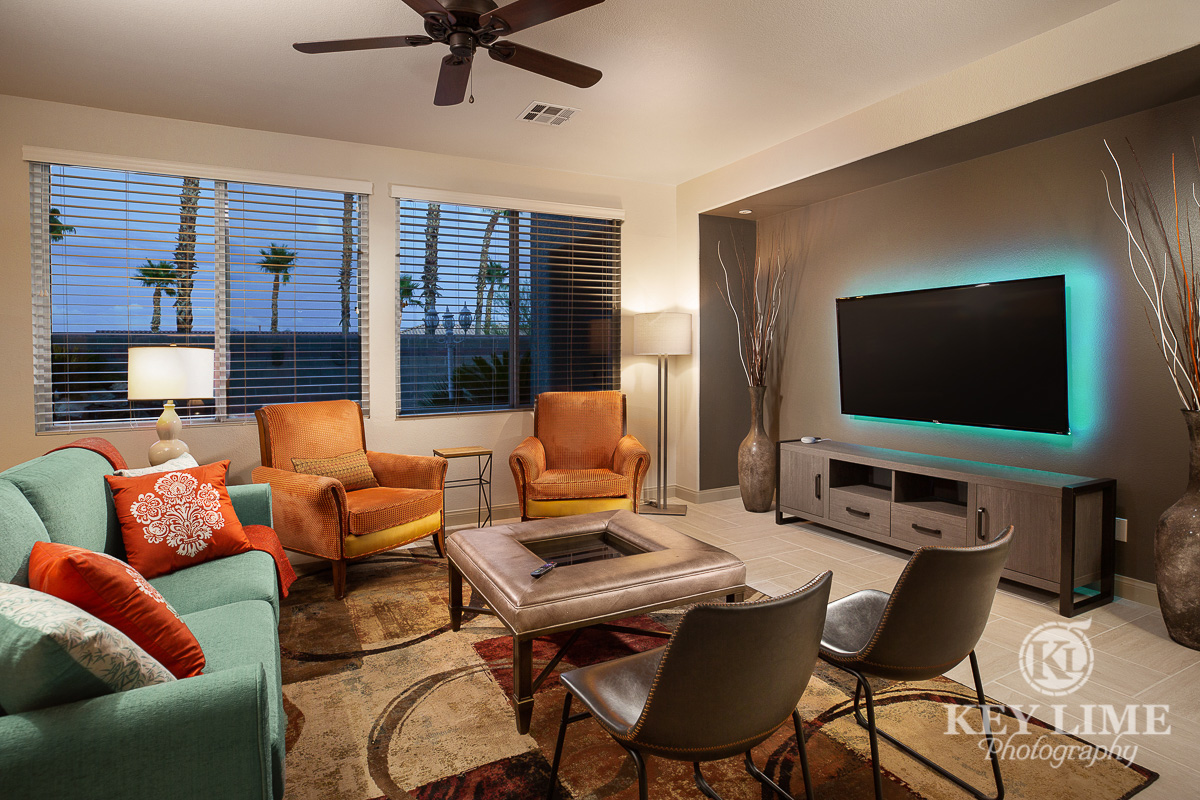 Real estate photo of a modern living room. Interior designer featured a green couch, orange chairs and leather detail table.