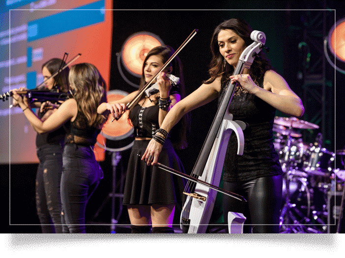 Las Vegas photographer image of women playing violin at a corporate business event. 4 women onstage, purple and orange lighting effects