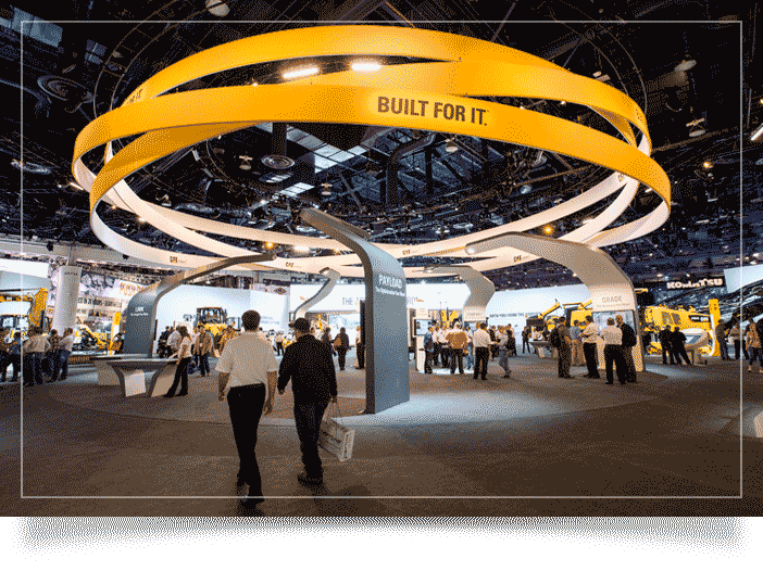 Trade show photography image of two men walking into a trade show. Large yellow rings hang from the ceiling in Las Vegas Convention Center
