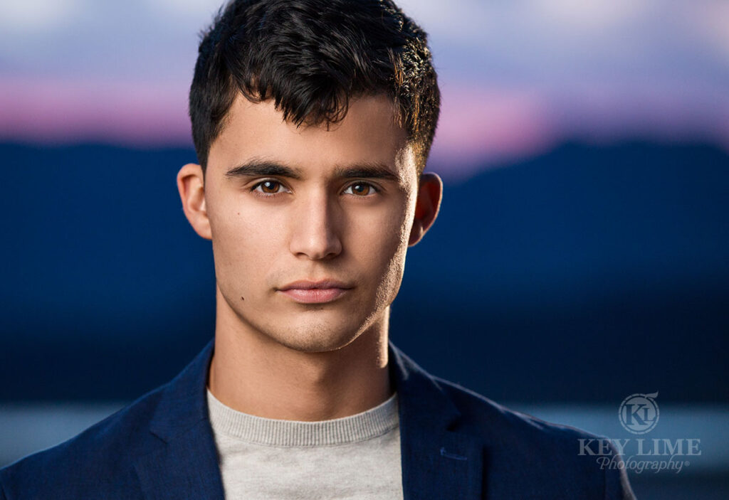 Headshot photographer image of young man with dark hair. Twilight hour with blue mountains and magenta glow.