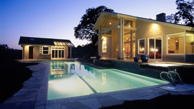 Custom home featuring an infinity pool lit up at night