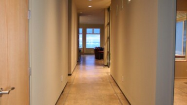 Custom home build features white walls with light-tone wood flooring