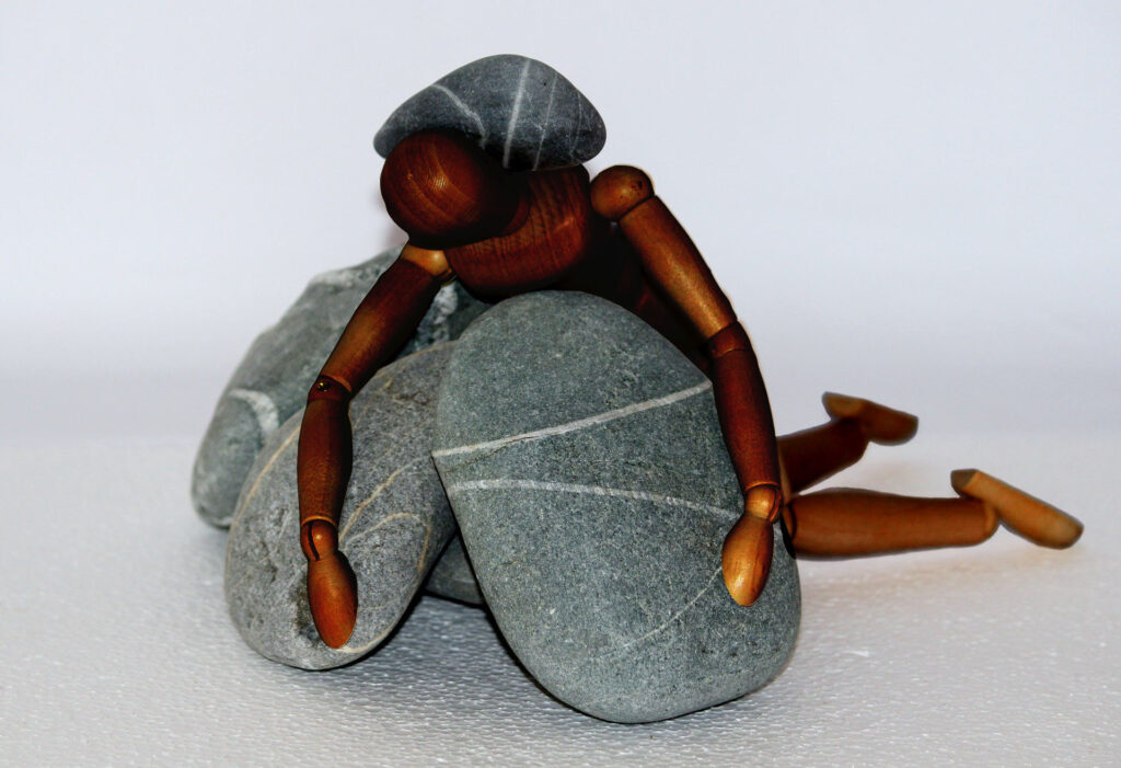 Illustration of a human being crushed on rocks