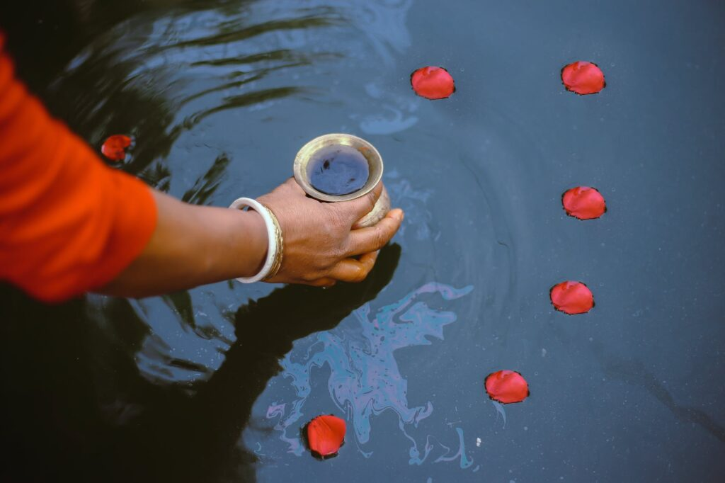Photo of flower petals and a jar in water.