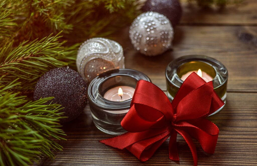 Picture of two small candles with greenery and a red bow