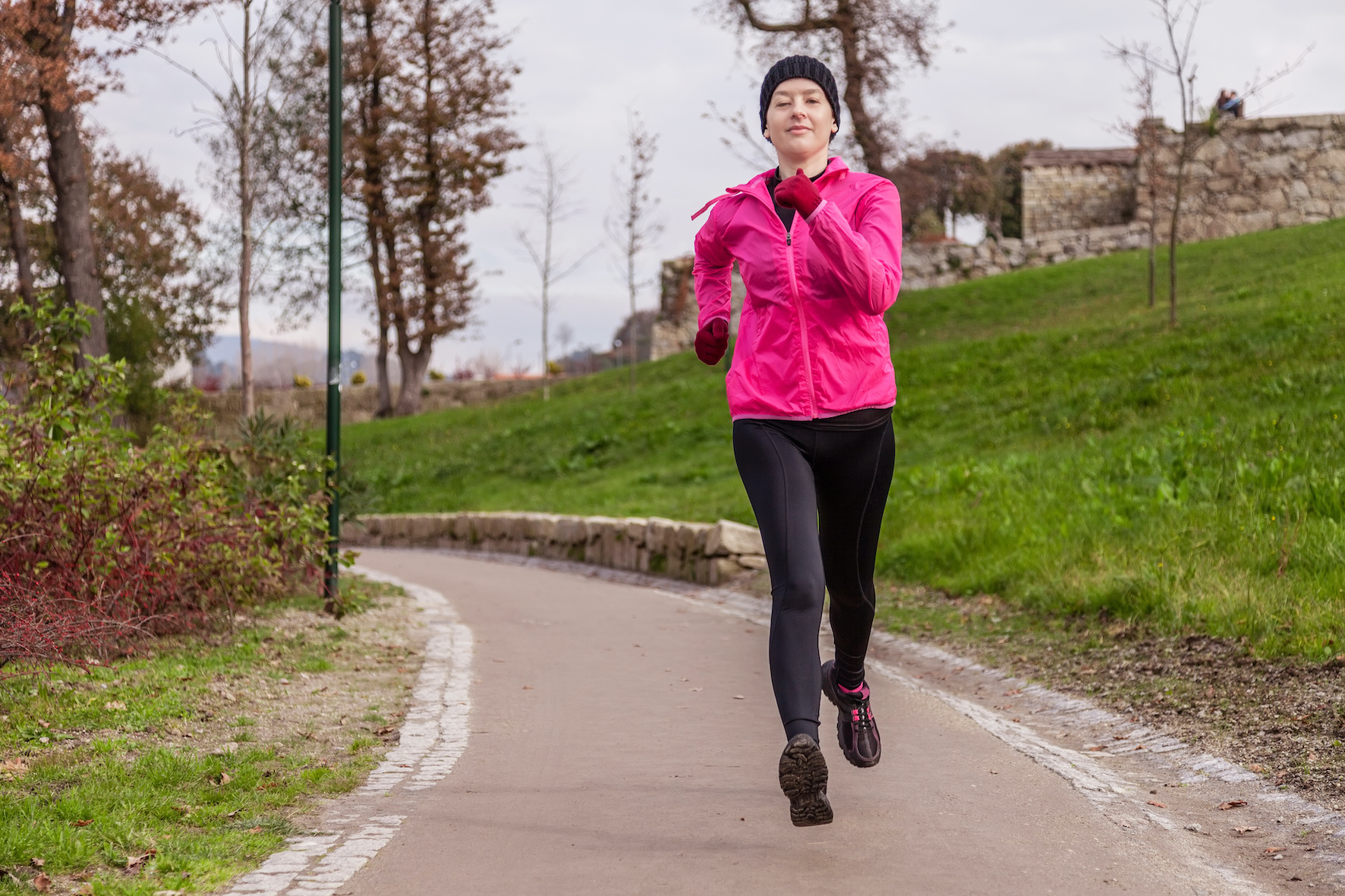 Young Woman Running On A Cold Winter Day In An Urban Park.