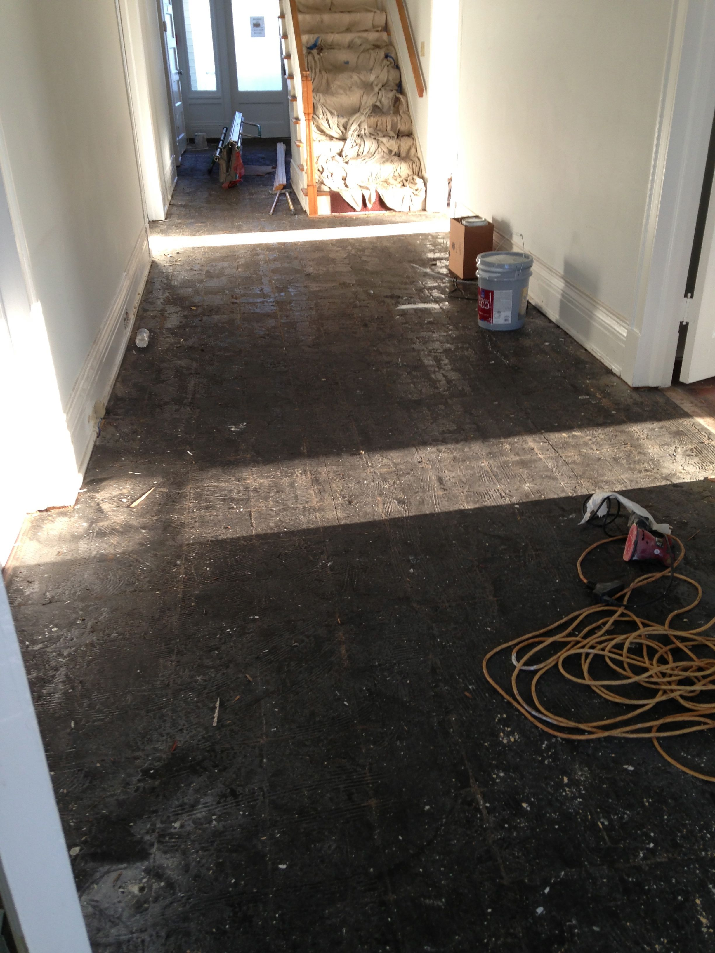 A picture of a tar covered hardwood floor after tile was removed.