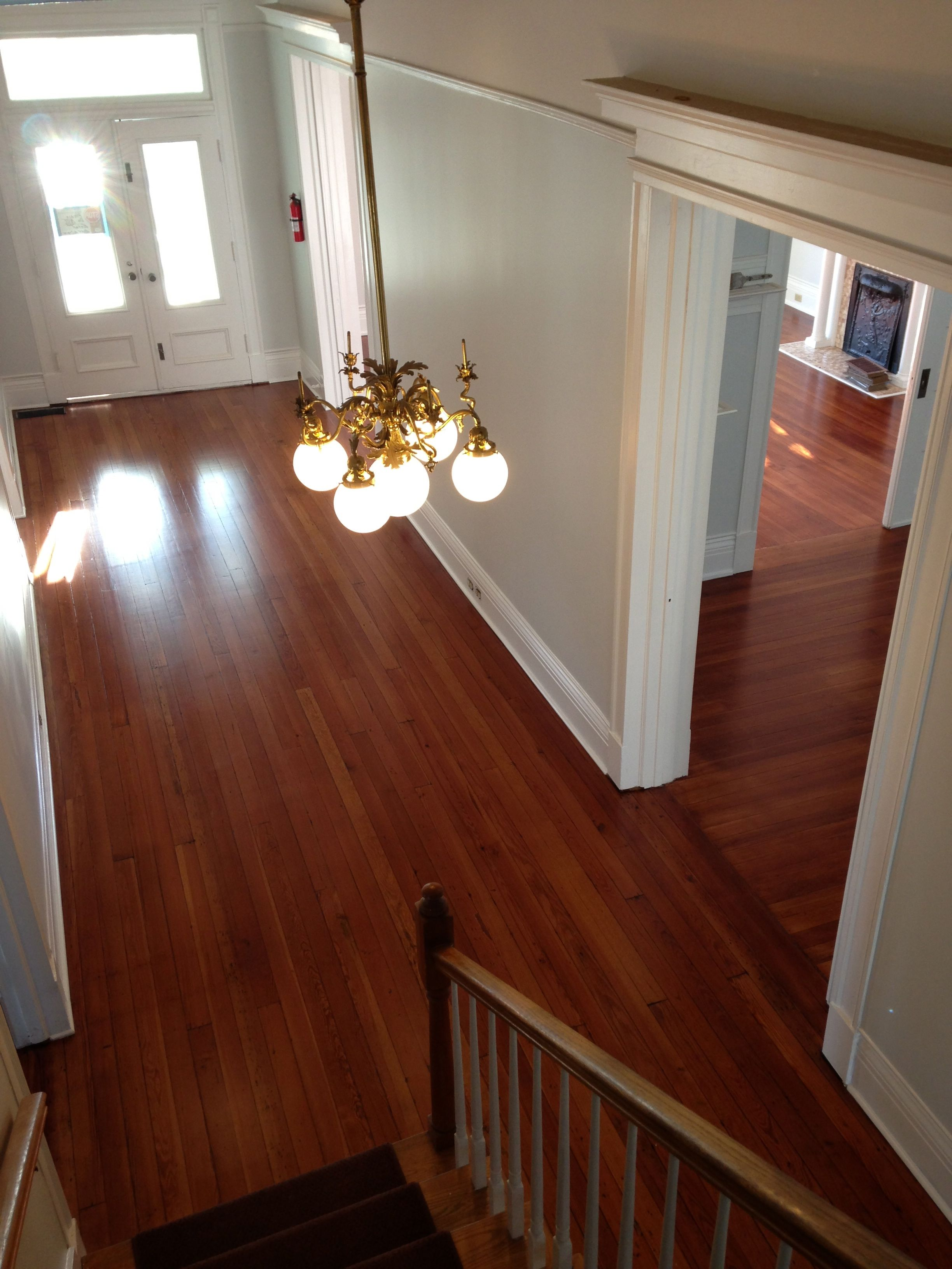 Photo from top of stairs view of an entry foyer of satin finished, red toned, hardwood floors that were previous cover with tar and tile.