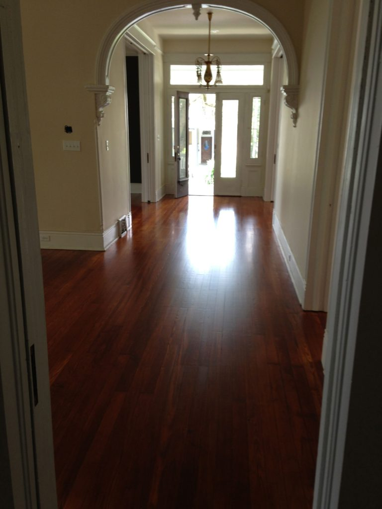 Refinished hardwood flooring in an arched foyer at front entrance