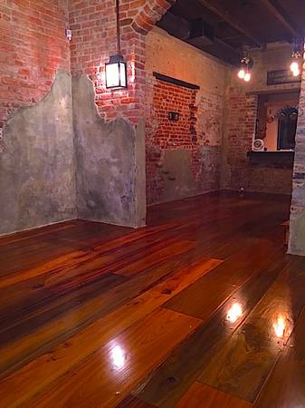 This is a photo of a historic cottage with wide planked shiny floors with shades of red and dark brown.
