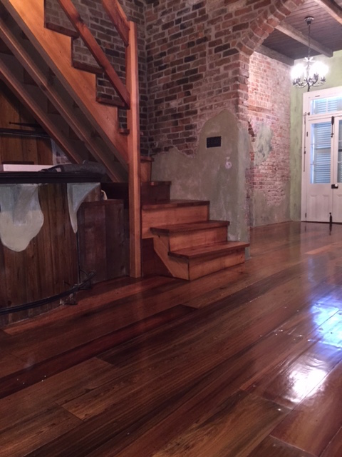 This is a photo of a historic cottage with wide planked pine hardwood floors with shades of red and dark brown. Sanded hardwood staircase is pictured.