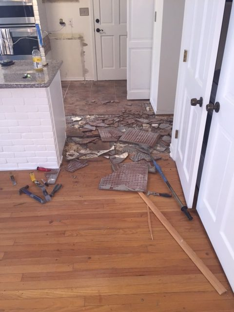 Photo of kitchen tile being removed. Pictures shows broken pieces of tile adjacent to a living room with hardwood flooring.
