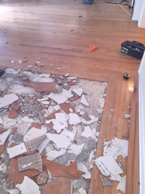 Photo of a square section of broken tile being removed and surrounded by hardwood flooring.