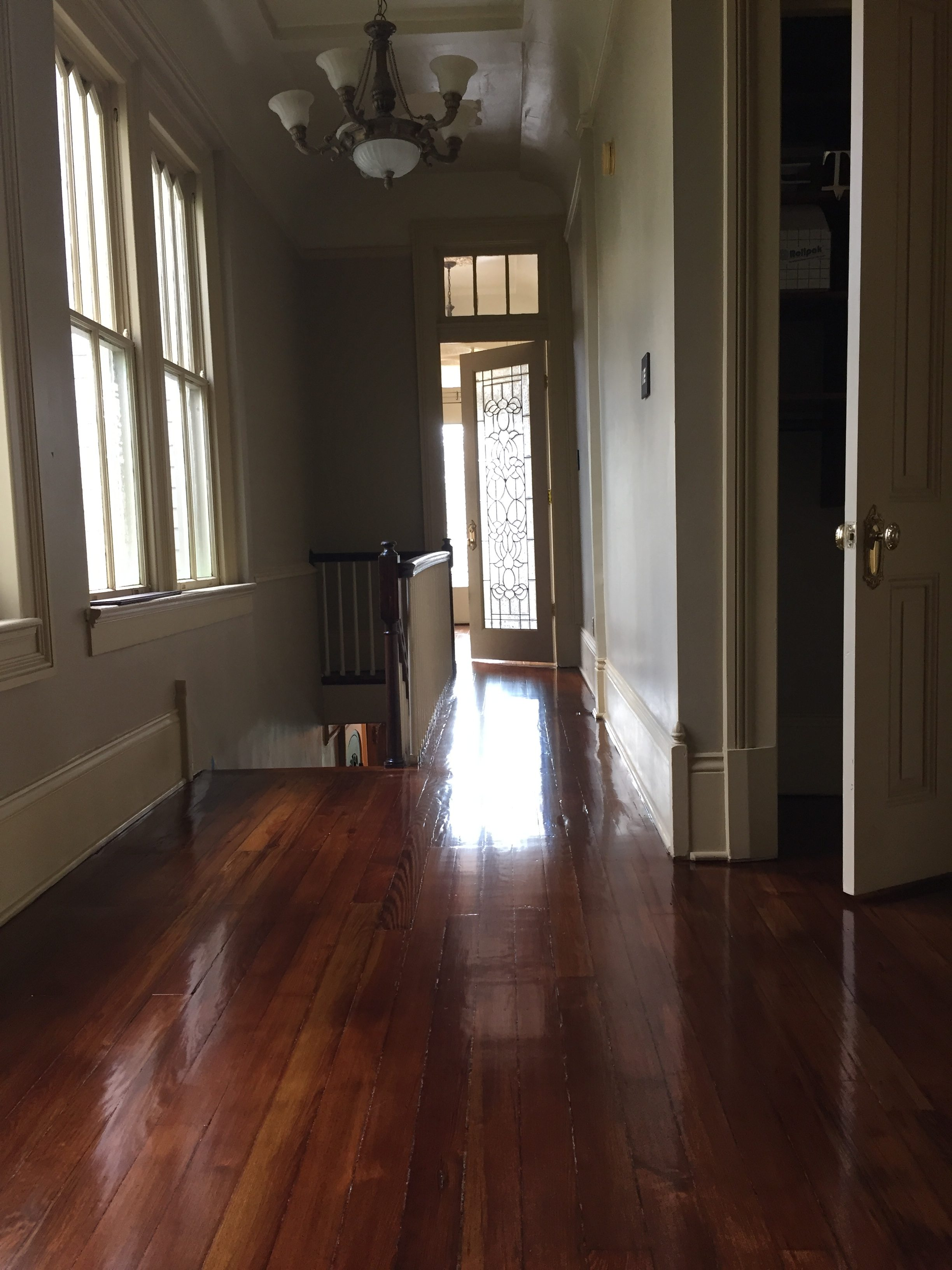 This is a hallway with a staircase of refinished glossy pine floors.