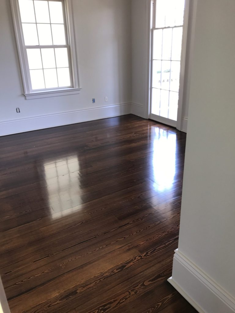 Pictured is a room with dark stained red pine hardwood flooring. It is glossy with the wood grain contrasts visible.