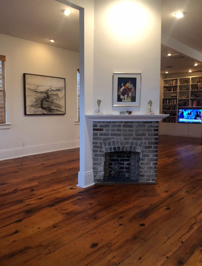 A living room photo with medium colored hardwood flooring prior to bleaching to a lighter color.