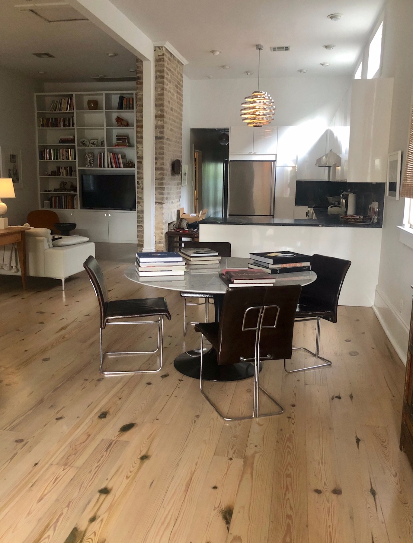 Photo of dining area hardwood flooring. It is bleached light with dark knots and has a custom stain.