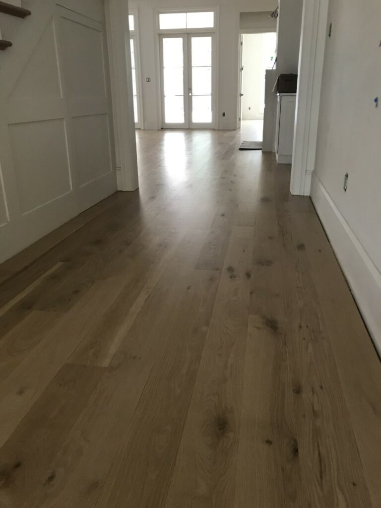 This is a photo of a hallway with white oak flooring with a satin finish. It has a weather washed appearance.