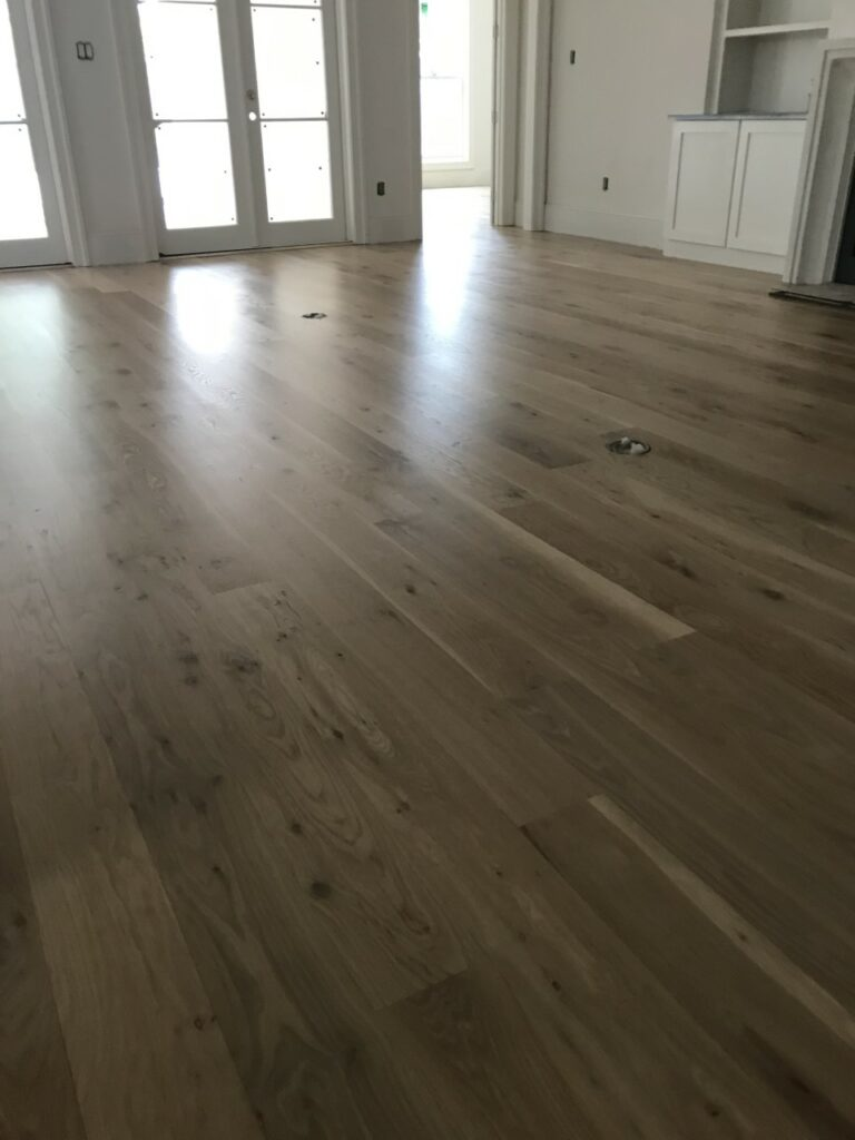 This is a photo of a living room with white oak flooring with a satin finish. It has a weather washed appearance.