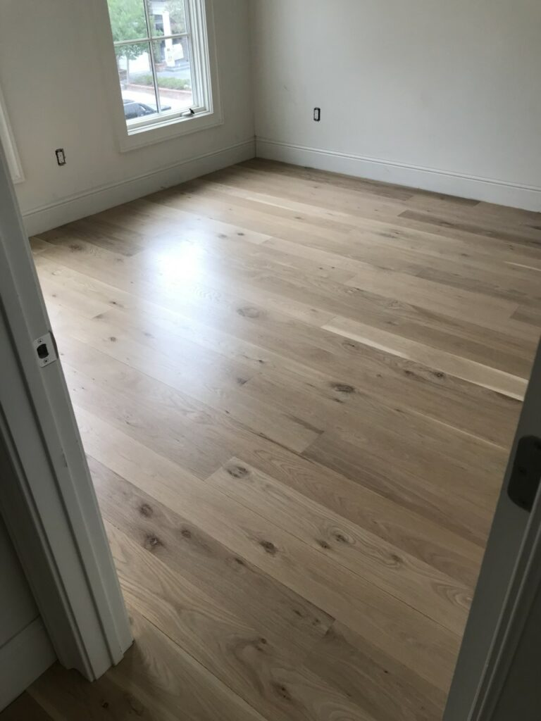 This is a photo of a room with white oak flooring with a satin finish. It has a weather washed appearance.